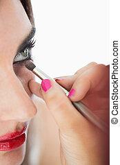 Woman making up smokey eyes with a brush