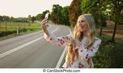 Woman making video call near countryside road.