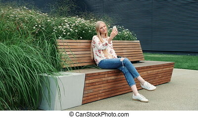 Woman making video call on green roof.