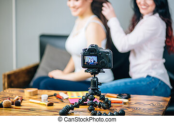 Woman making video for her blog on cosmetics using tripod...