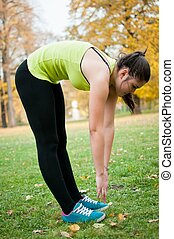 Woman making warm up before sport in park