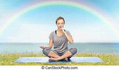 woman making yoga meditation in lotus pose on mat - fitness,...