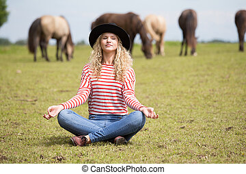 Woman making yoga on horse meadow