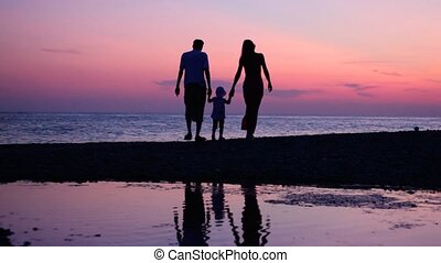 woman, man and little girl having joined hands walking on sunset sea coast