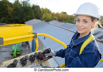 woman maneuvering cherry picker above warehouses