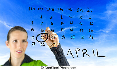 Woman marking Earth Day on a calendar