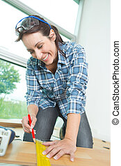 Woman marking line on wood