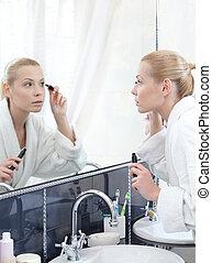 Woman mascaras her eyelashes