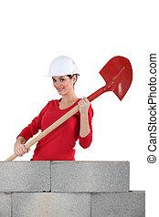 Woman mason holding a shovel