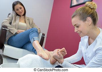 woman massaging female feet