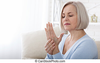 Woman massaging her arthritic hand and wrist closeup