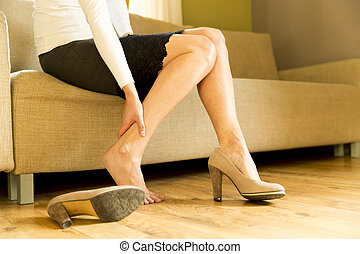 70b3ba571 Woman massaging her legs after wearing high heels all day at work in office