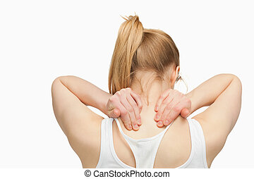 Woman massaging her nape with her hands against white...