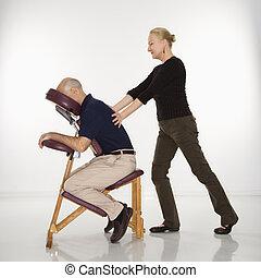 Woman massaging man. - Caucasian middle-aged female massage...