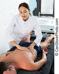 Woman masseur working in spa