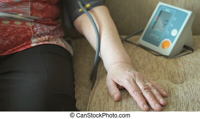 Old woman measures arterial pressure using a blood pressure cuff sitting on a beige sofa