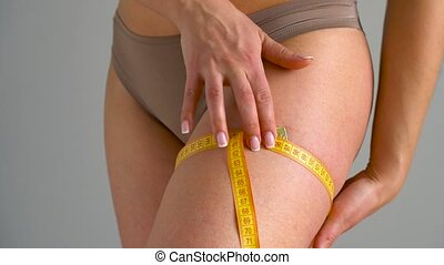 Woman measures her leg with measuring tape