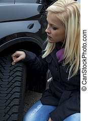 woman measures tire profile of a car tire