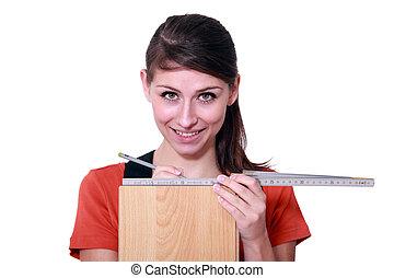 Woman measuring a floor board