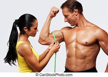 Woman measuring athletic's man biceps.