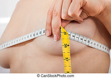 Closeup photo of woman measuring her breasts