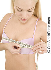 woman measuring her breast with a tape
