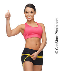 woman measuring her hips - picture of sporty woman measuring...