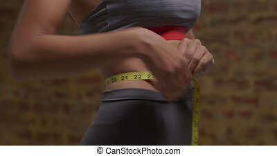 Woman measuring her waist - Front view mid section of a ...
