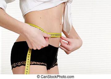 Woman measuring her waist with