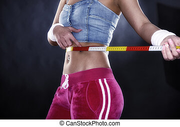 Woman measuring her waistline. Perfect slim body. Diet and sport