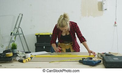 Woman measuring plywood sheet with spirit level - Beautiful...