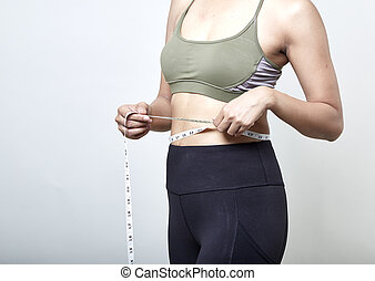 Woman measuring shape of beautiful waist