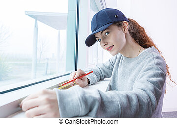 woman measuring the window pane