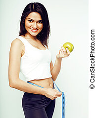 woman measuring waist with tape on knot holding green apple happy smiling, lifestyle healthcare people concept