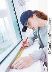 Woman measuring window sill