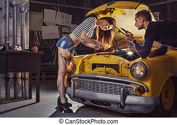 Woman mechanic in sexy shirts is repairing an old car. Car owner is looking at her.