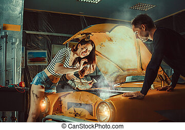 Woman mechanic in sexy shorts is repairing an old car.