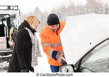 Woman mechanic looking under car hood snow assistance winter...