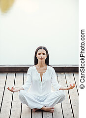 Woman mediating. Beautiful young woman in white clothing sitting in lotus position and keeping eyes closed while meditating outdoors