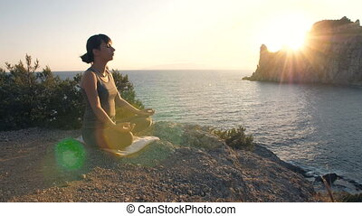 Woman meditates against the sea