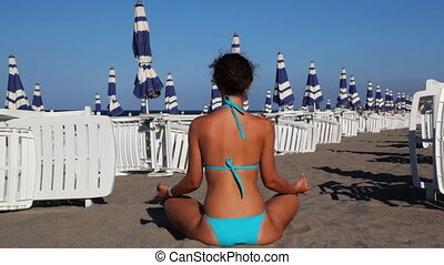 Woman meditates in lotus position on beach