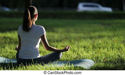 Woman meditates in the park against the traffic