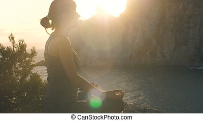 Woman meditates on nature at sunset