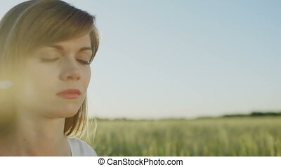 Woman meditates outdoor, while eyes closed
