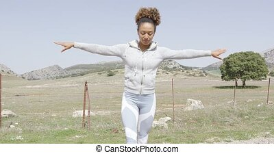 Woman meditating among nature - Young woman wearing sport...