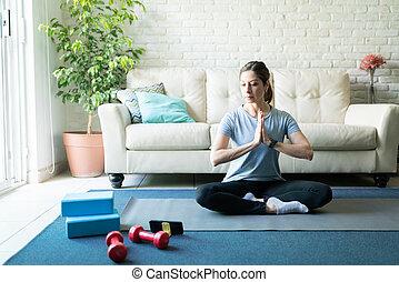 Woman meditating and doing yoga at home