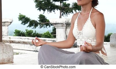 Woman meditating and doing yoga in abandoned temple. Female practicing pose
