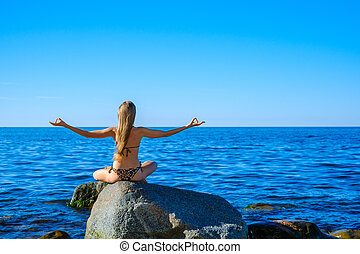Woman meditating at morning near sea