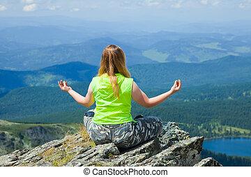 Woman meditating at mountain peak