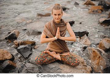 Woman meditating at the beach . yoga retreat. namaste in...